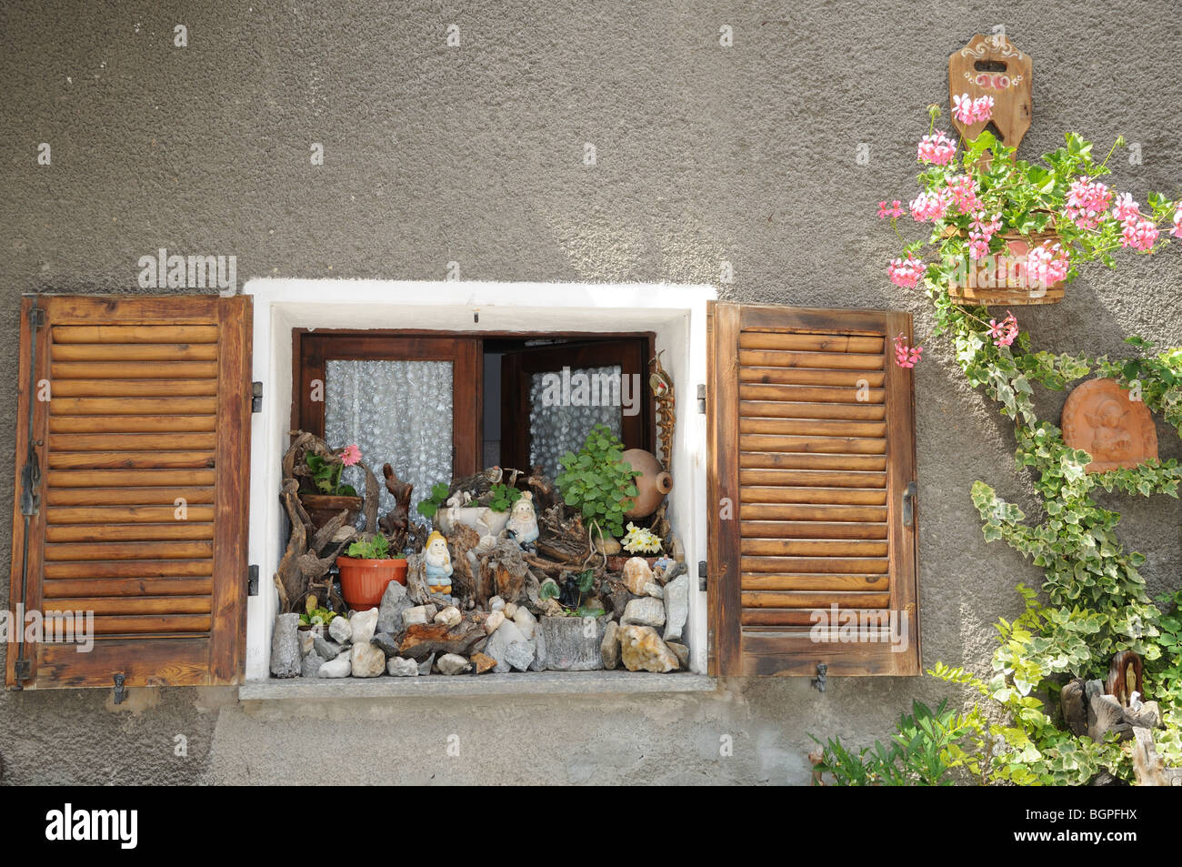 Charming window sill decorated with pepples stones flowers window box gnomes Pont St Martin Aosta Valley Italy Stock Photo