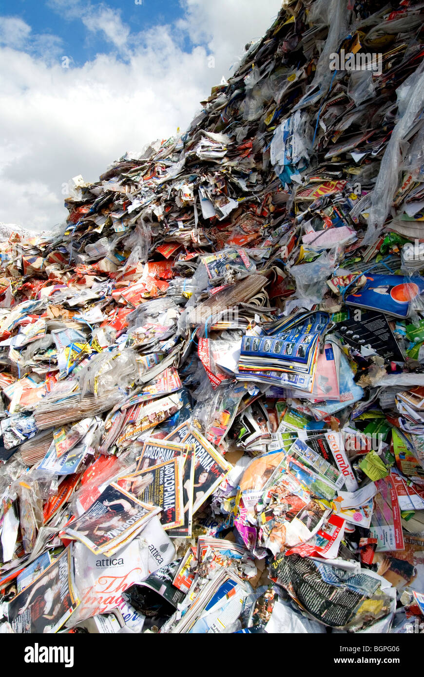 Heaps of recyclable paper, magazines, books stored at the yard of the paper recycling factory ready to be processed - Stock Image