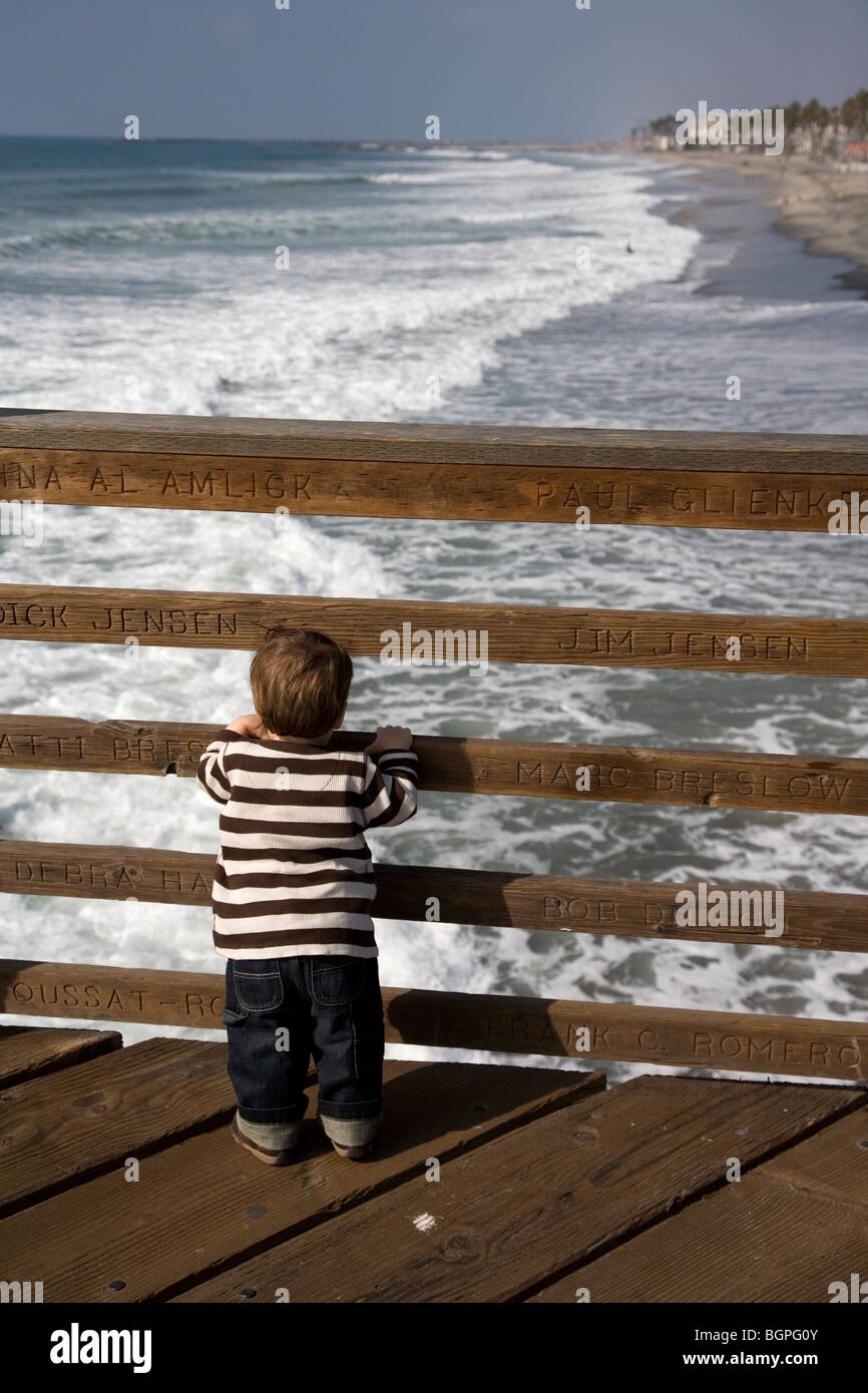 18 month old boy looking at ocean, Oceanside Pier, Oceanside, California - Stock Image