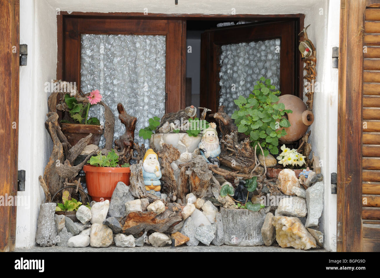 Charming window sill decorated with pepples stones flowers window box gnomes Pont St Martin Aosta Valley Italy - Stock Image