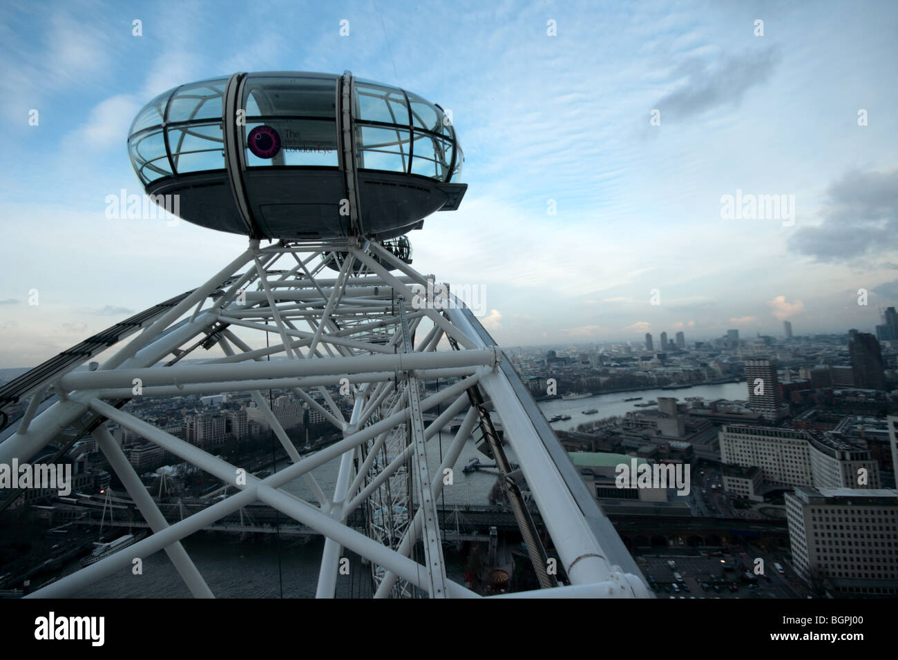 A london eye pod slowly rotates into the december sunset - Stock Image