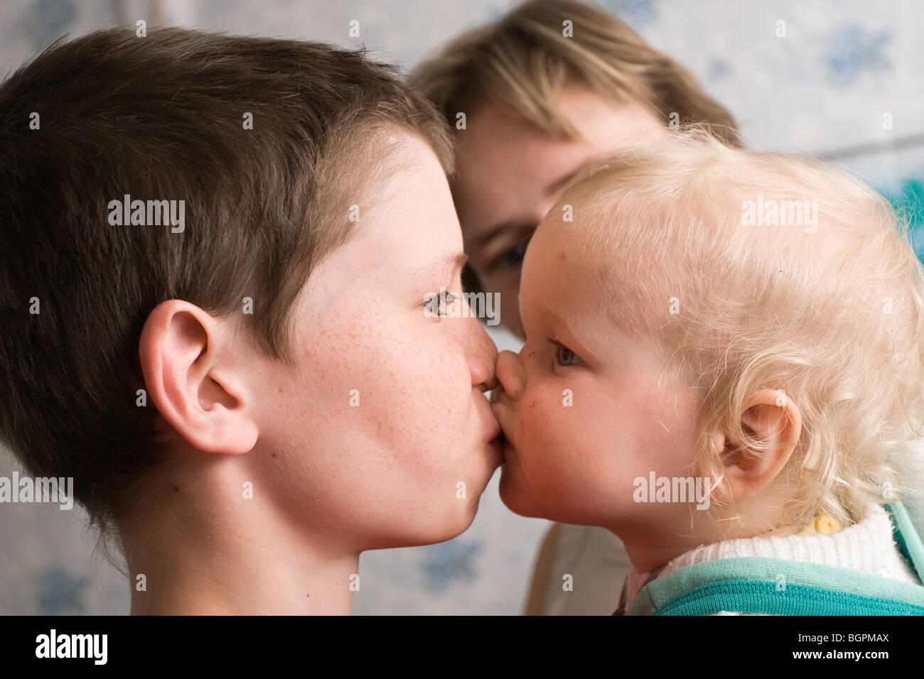 Boy kissing girl on lips in a bath, black girl jewelry