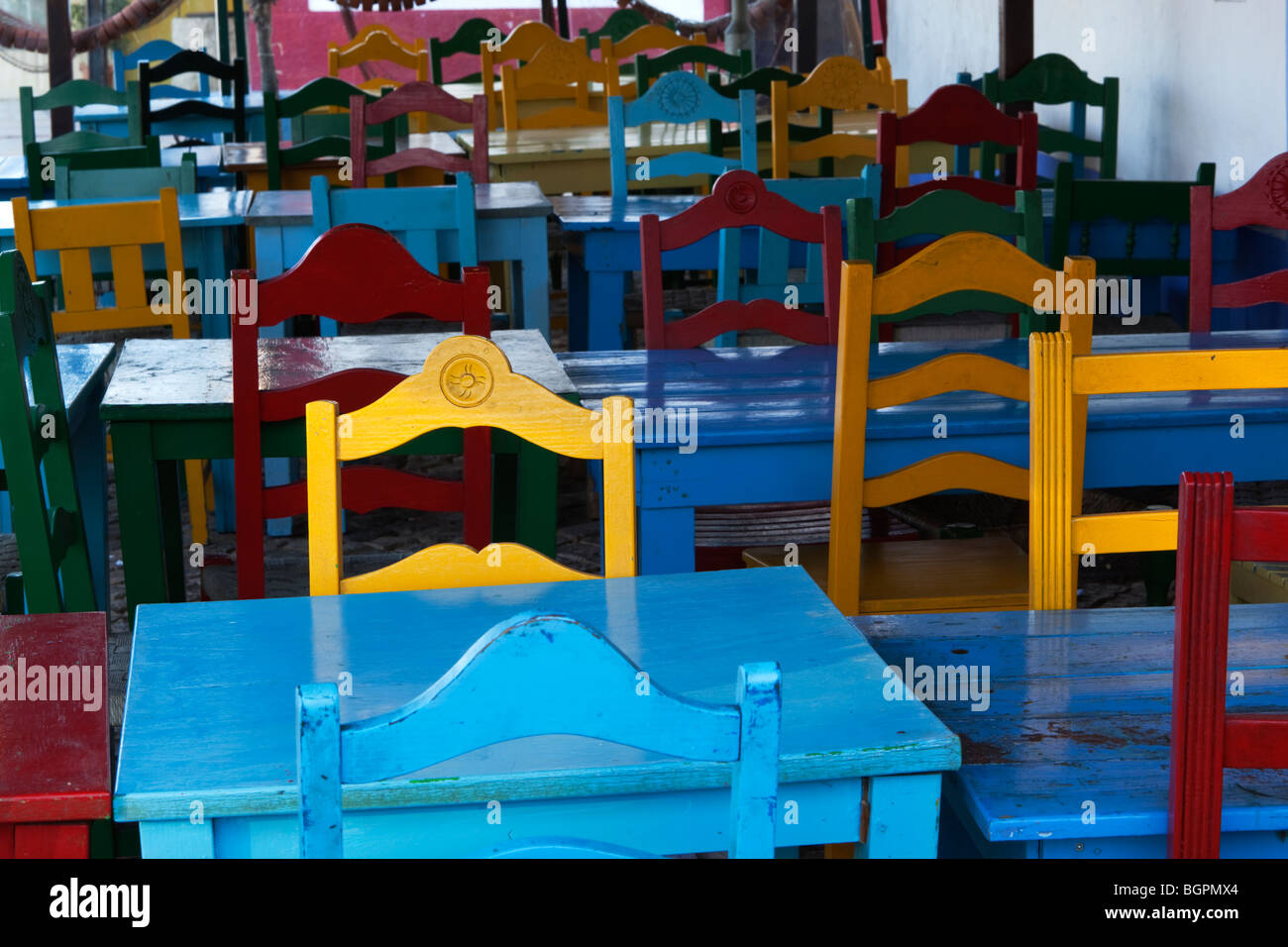 rows of colourful tables and chairs - Stock Image