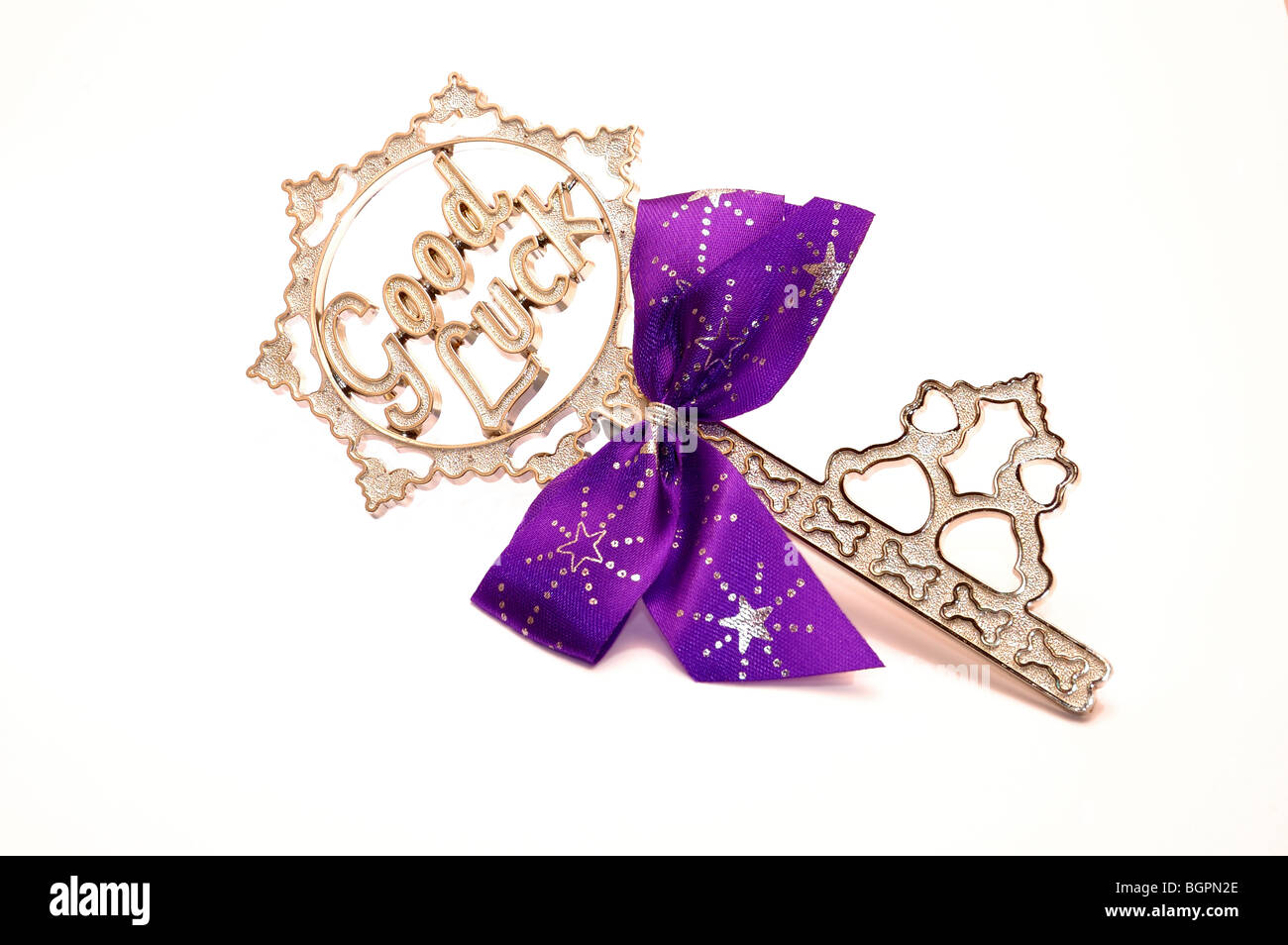 Large silver key with the words good luck and a purple ribbon on a white background - Stock Image