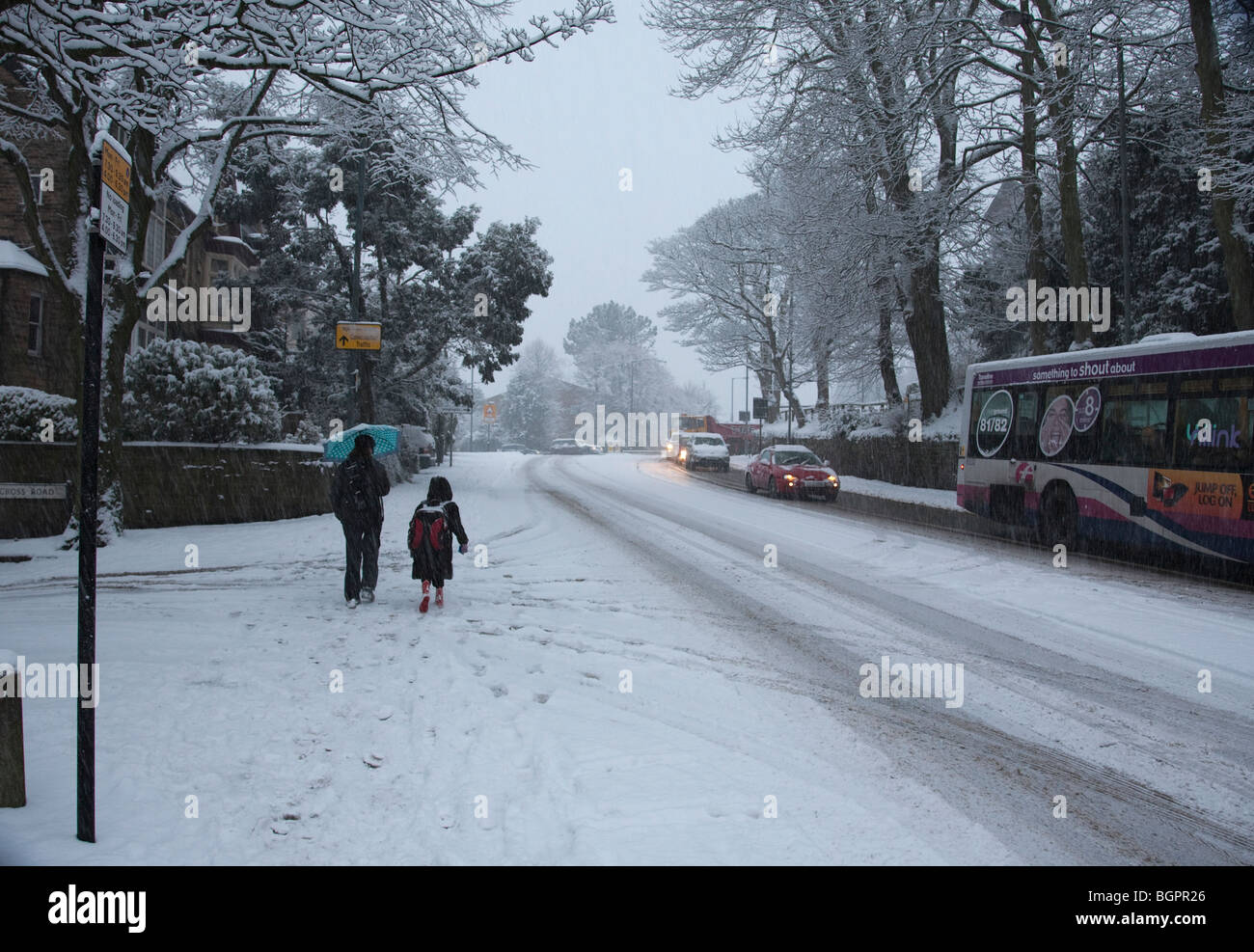 Mother and daughter walking to school in extreme winter