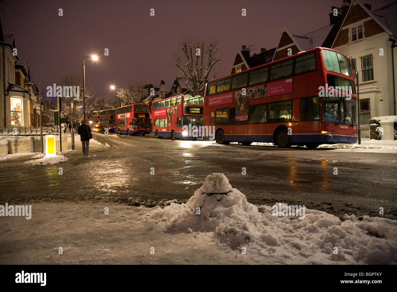 A line of out-of-service buses parked along Muswell Hill Road during the record-breaking icy cold spell in London, - Stock Image