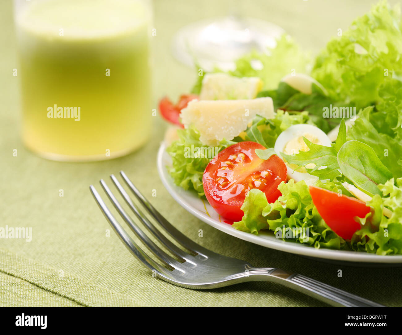 Fresh salad with tomato and quail eggs in a white bowl on a green tablecloth Stock Photo