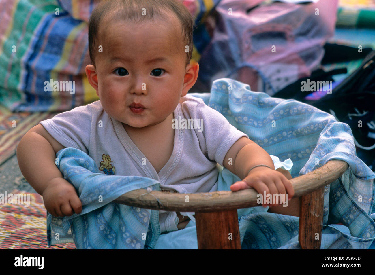 At evening street market in Luang Prabang, vendor's baby in a basket sports an impish grin. Laos, Southeast - Stock Image