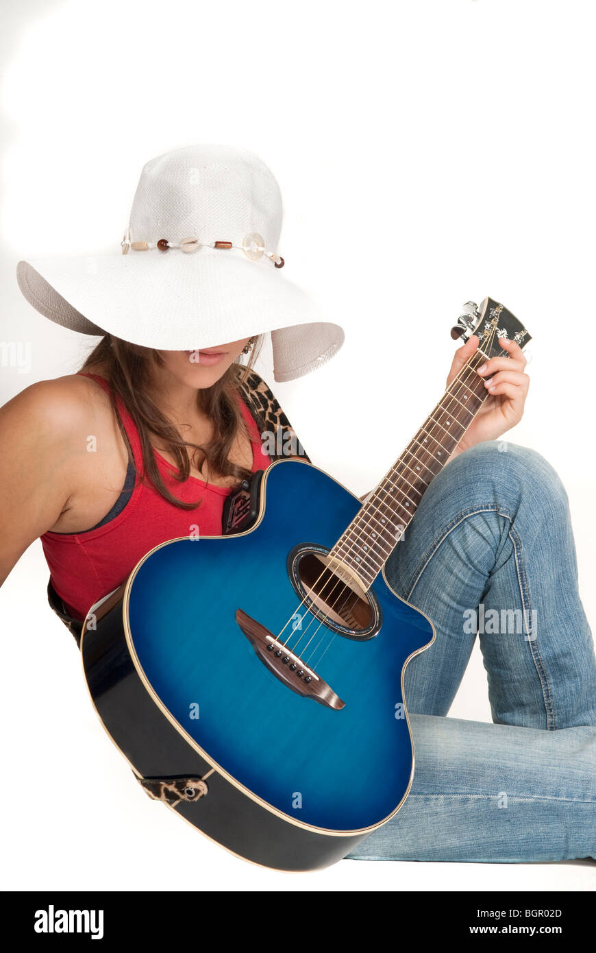 a young girl smiling, holding a guitar - Stock Image
