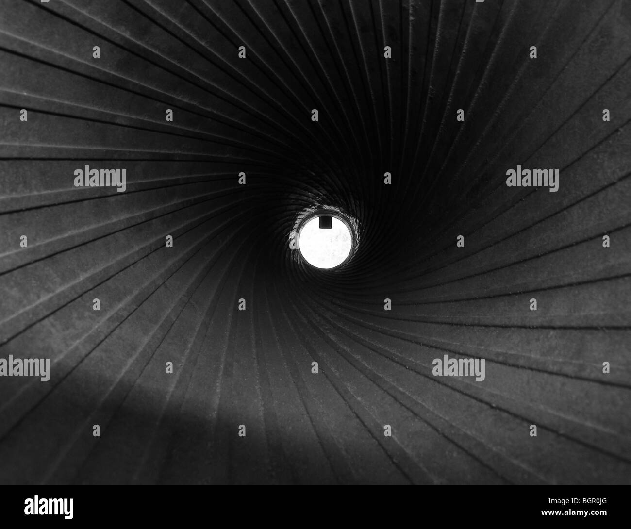 White disk with shiny steel spirals of rifling, view of cannon barrel on the inside, monochrome image - Stock Image