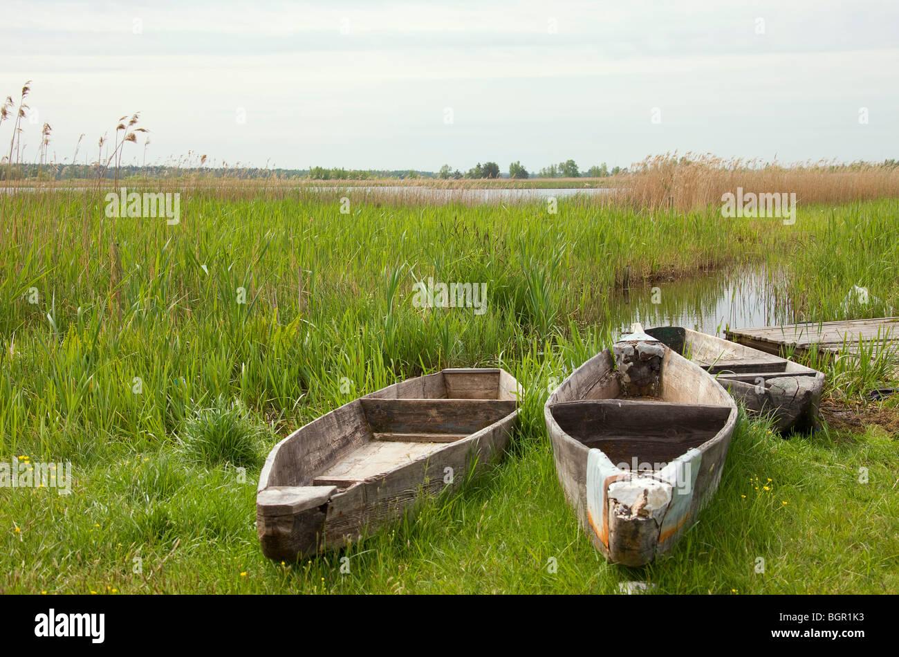 Old Polish punts, flat-bottomed canoes, on shore of lake. - Stock Image