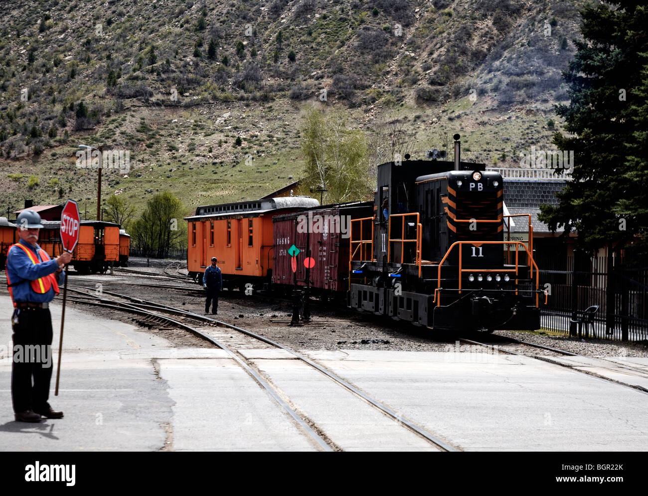 Crew stopping traffic while the historic narrow gauge railroad Durango-Silverton train crosses East College Drive, - Stock Image