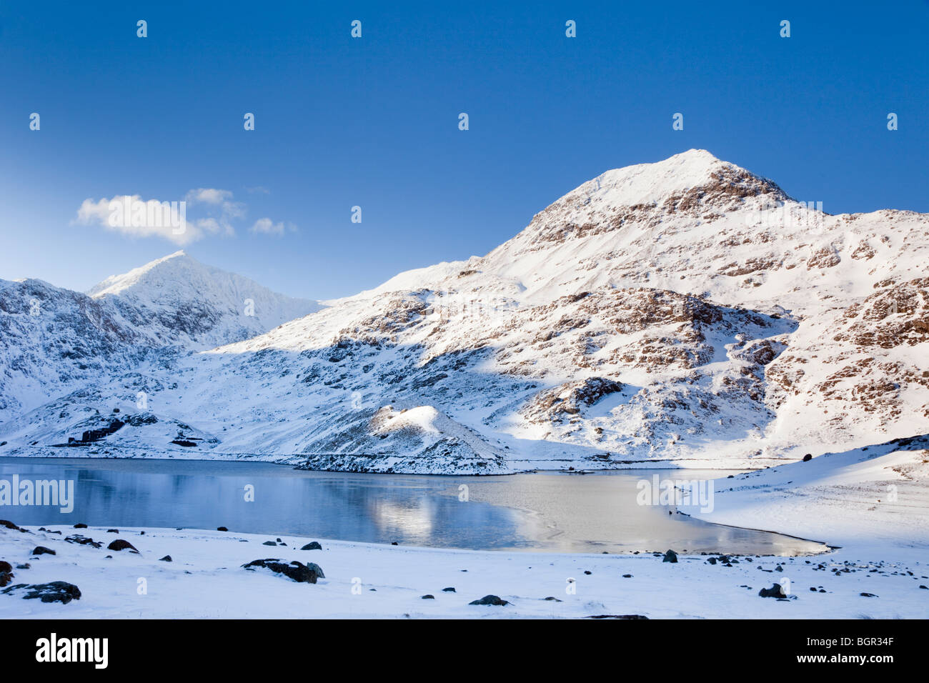 Llyn Llydaw lake with Crib Goch and Mount Snowdon mountain peak with snow in winter from Miners Track in Snowdonia National Park Eryri North Wales UK Stock Photo