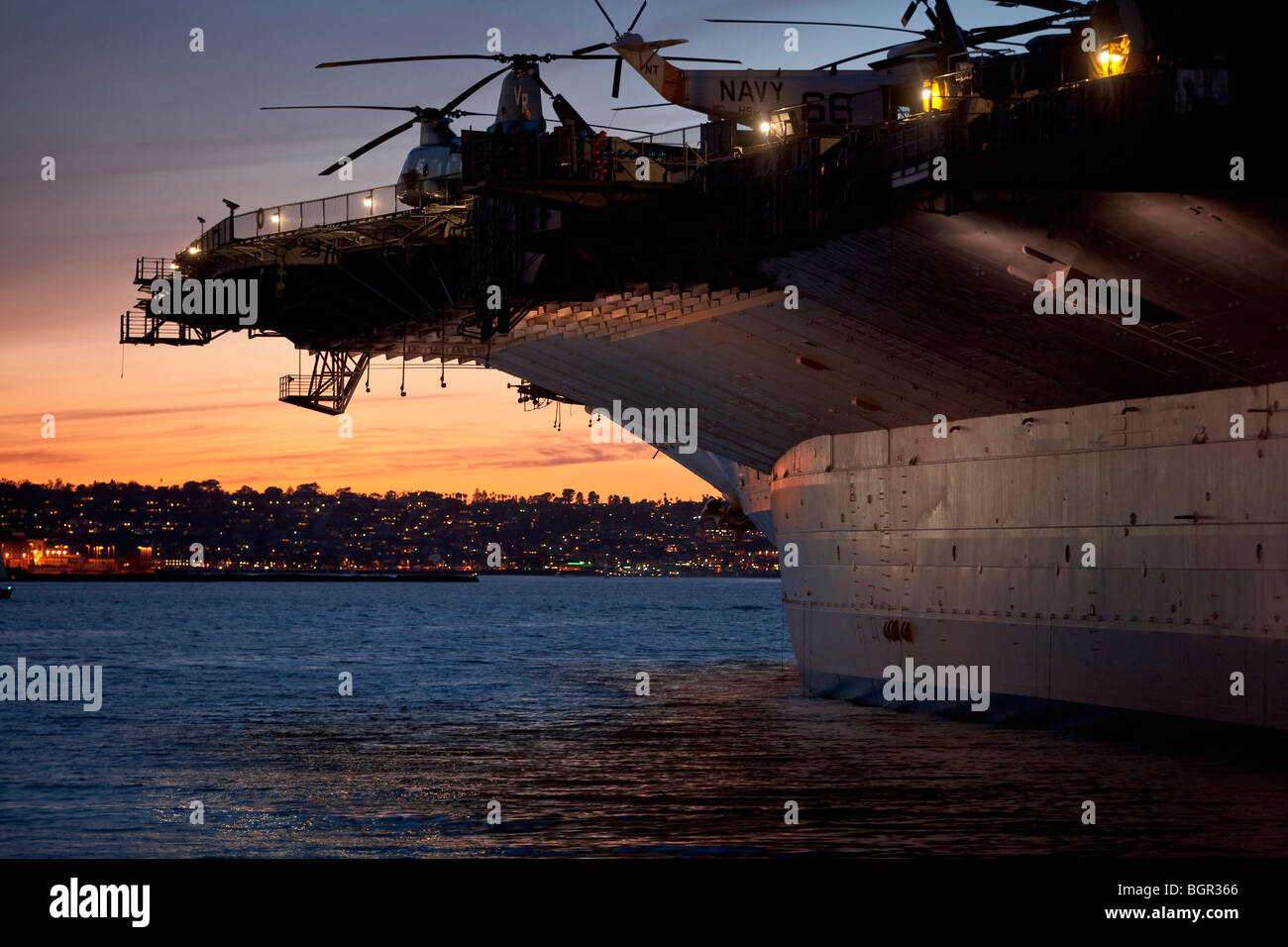 Aircraft carrier in San Diego harbor at sunrise, San Diego Bay, California, USA - Stock Image