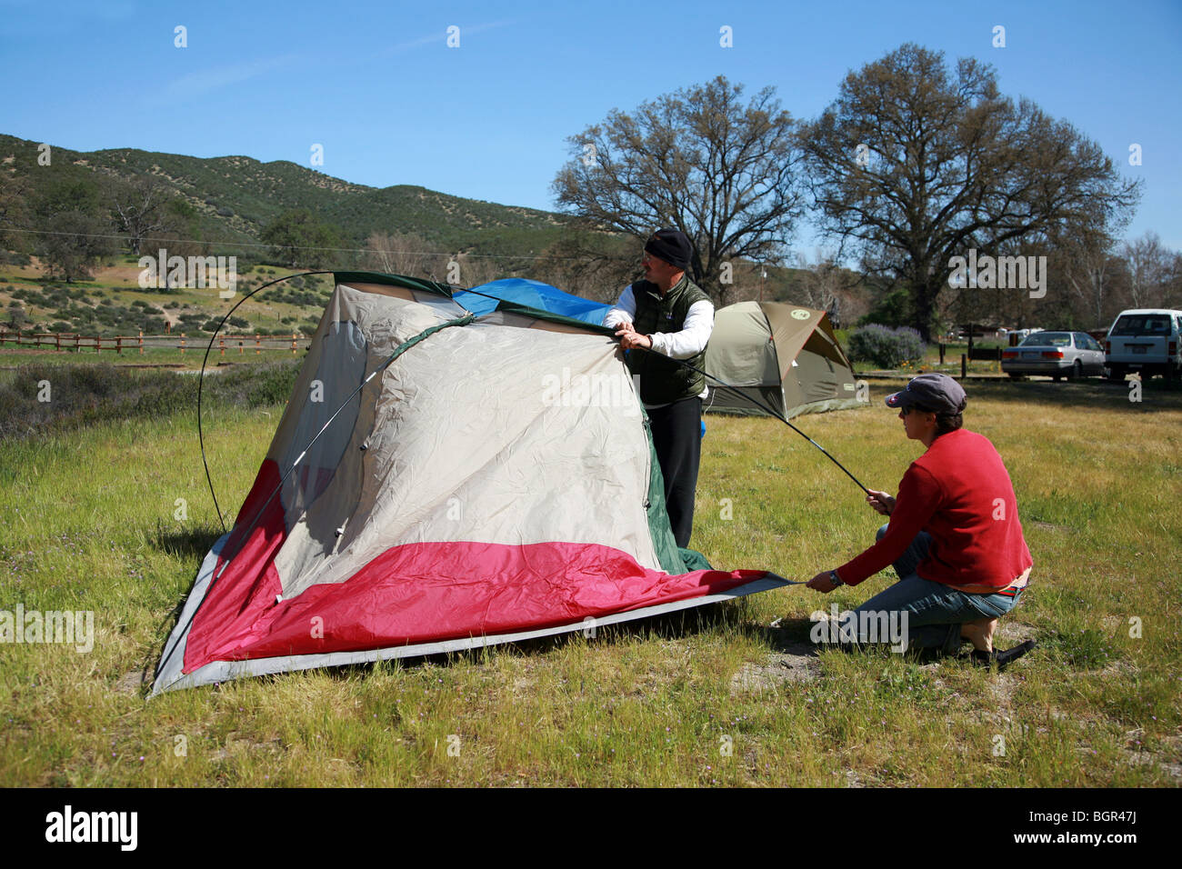a man and woman camping and building a tent outdoors stock photo