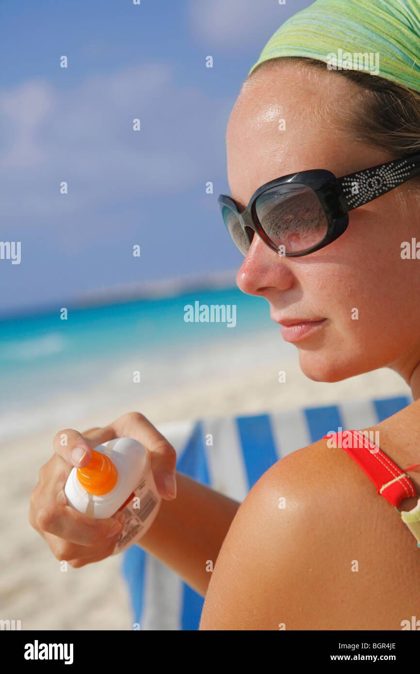 Woman applying sun tan cream on the beach in Playa del Carrmen, Mexico - Stock Image