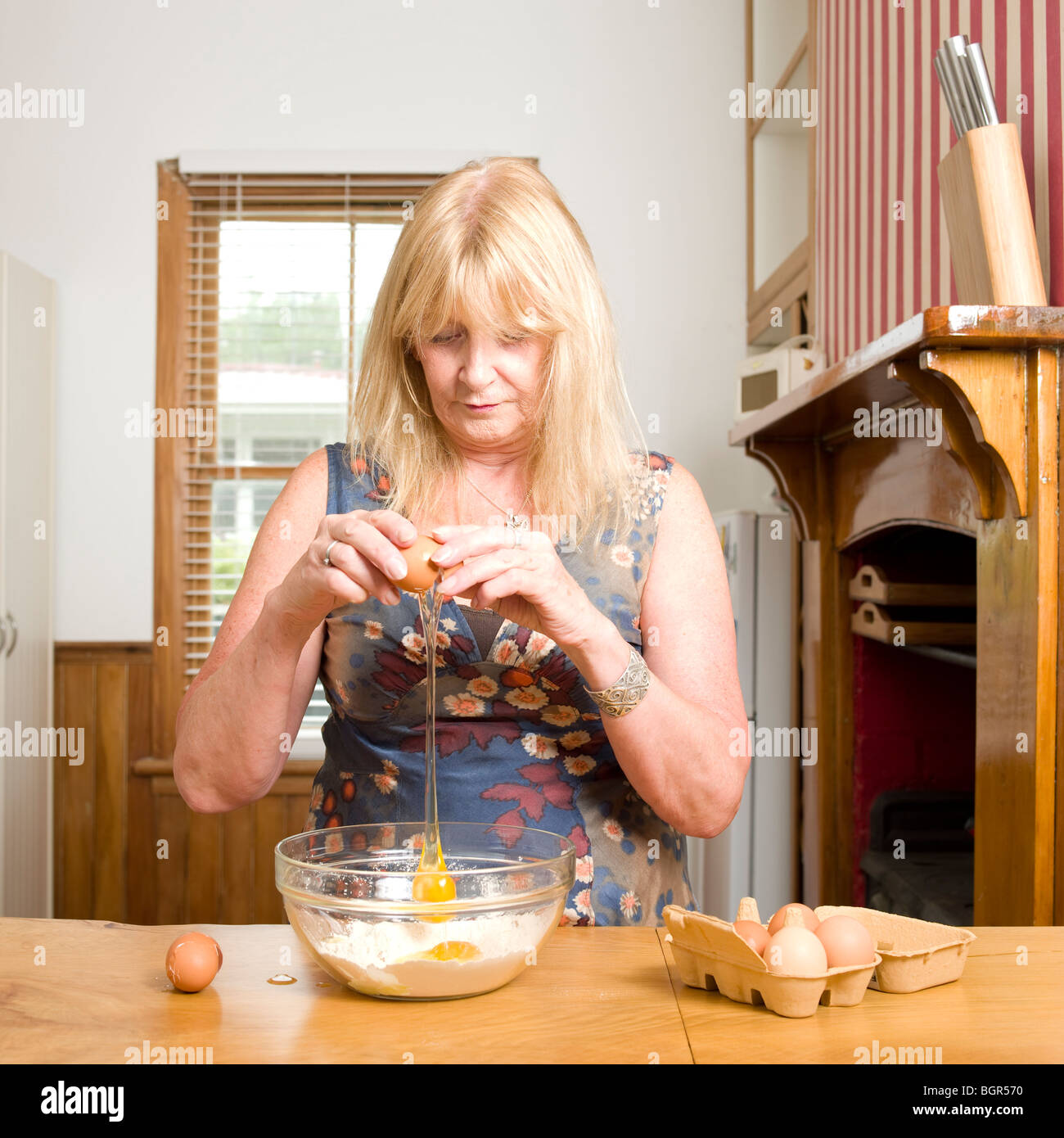 women cracking eggs into mixing bowl of flour with eggs shell next to bowl - Stock Image