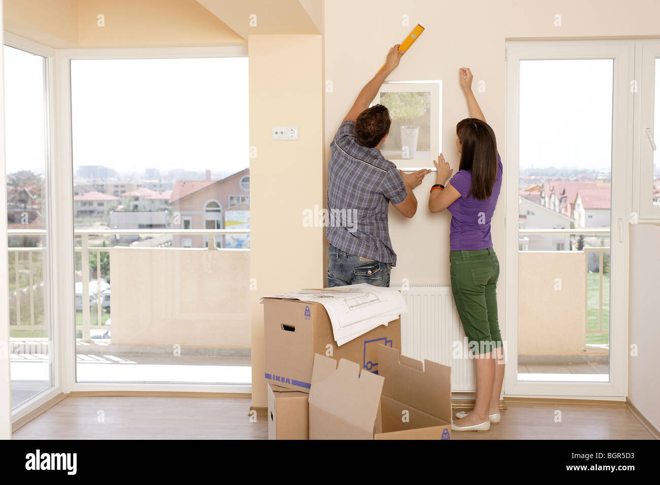 man and woman just moving in decorating a new apartment Stock Photo ...