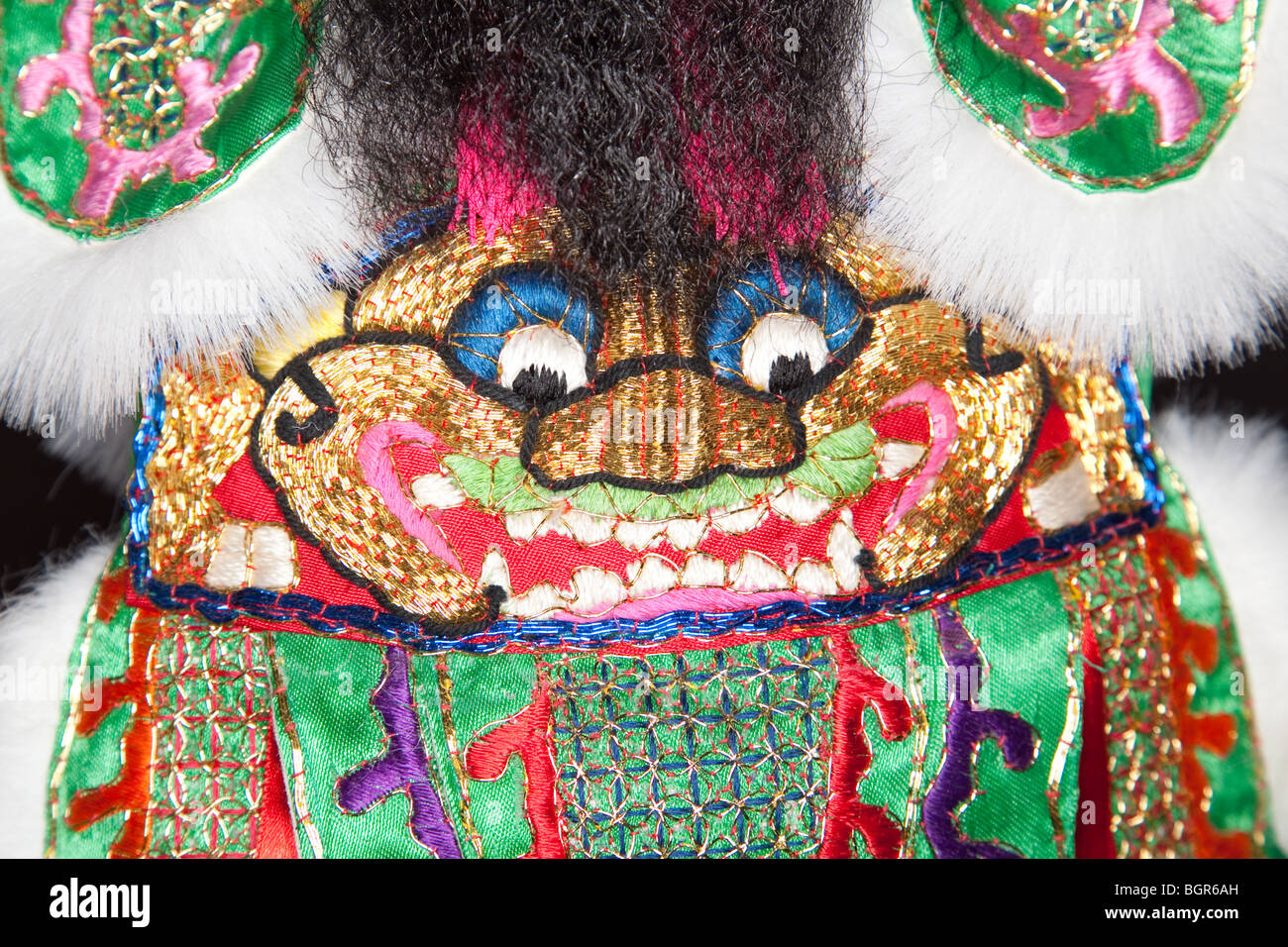 Closeup of a handmade Chinese ornamental robe sporting the face of a lion - Stock Image