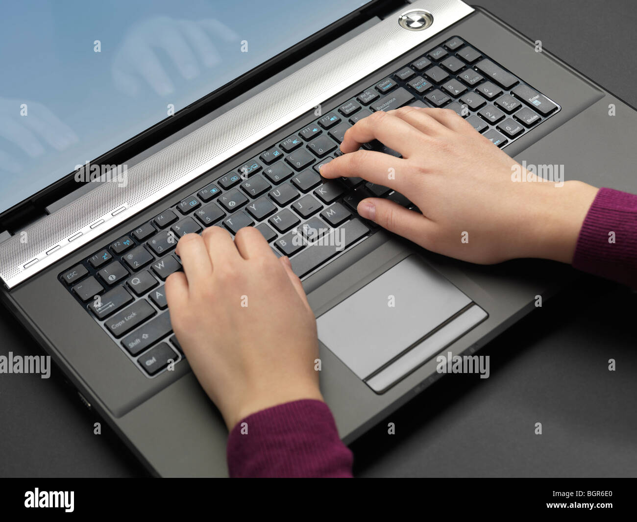 Woman typing on a laptop computer keyboard - Stock Image