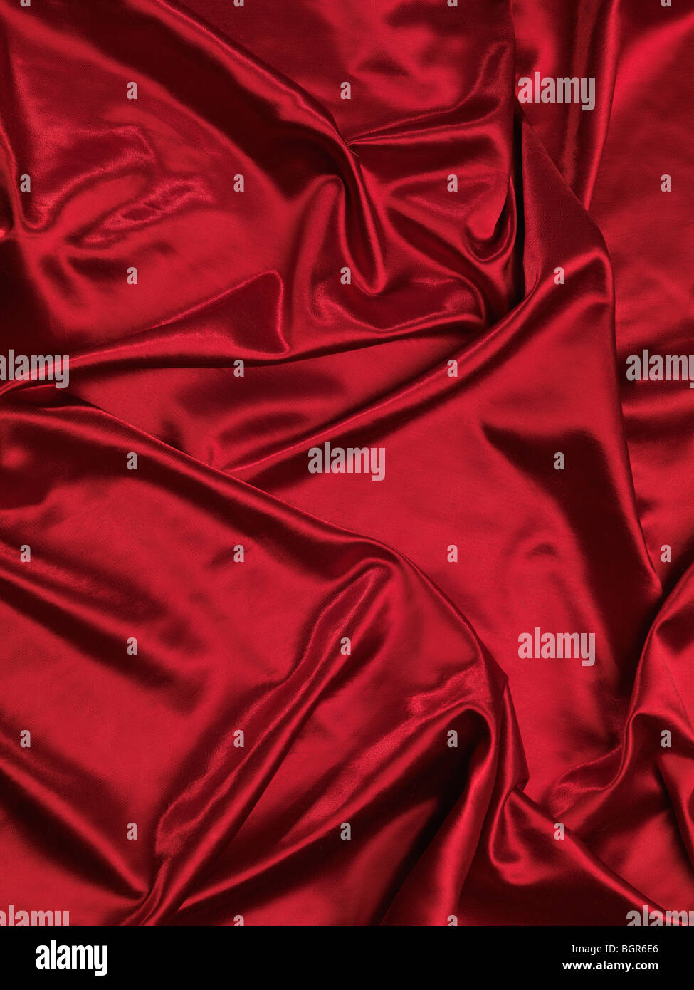 Red shiny silky fabric background - Stock Image
