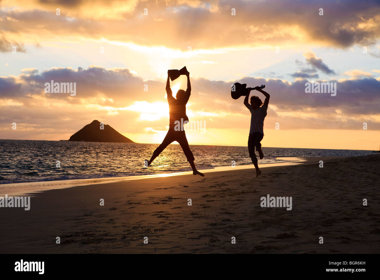 silhouette of twin brothers with drum and guitar leaping in the air at sunrise on a hawaii beach - Stock Image