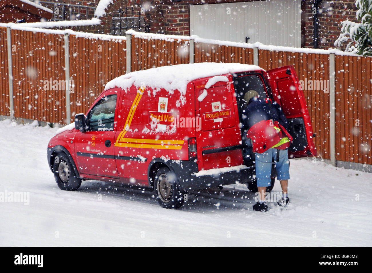 Royal Mail delivery van and postman in residential street during snow storm (number plate obscured) - Stock Image