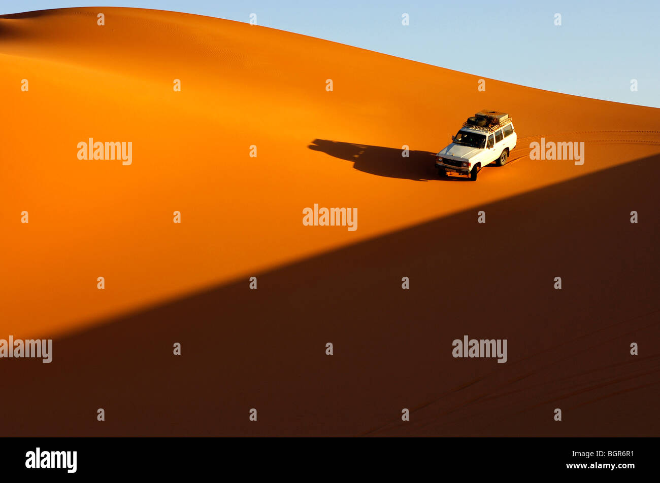 Four-wheel drive car driving at sunset on the pristine slope of a sand dune in the Erg Muzuruq of the Sahara desert, - Stock Image
