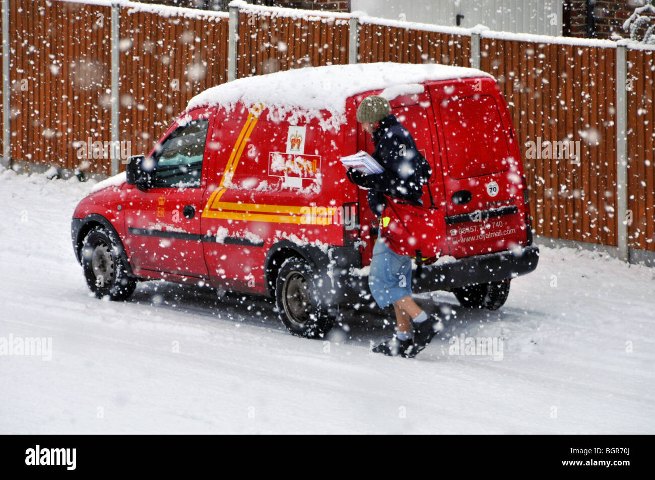 Royal Mail delivery van and postman walking residential street during snow storm (number plate obscured) Brentwood - Stock Image