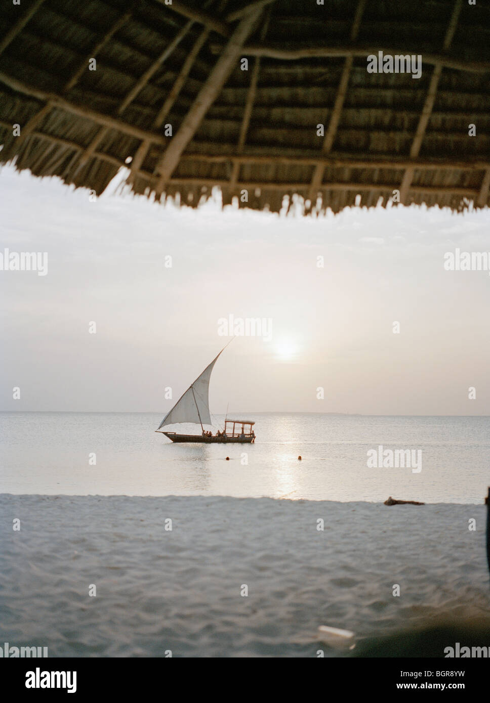 A sailboat passing by a beach - Stock Image