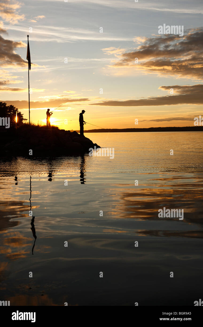 Silhouette of two persons fishing in the sunset, Sweden. - Stock Image