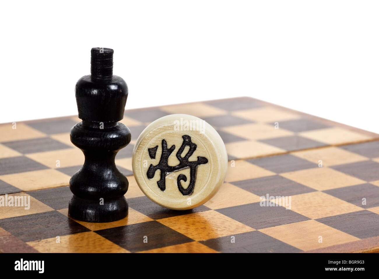 Western and Chinese Chess pieces facing each other depicting cultural difference between East and West - Stock Image