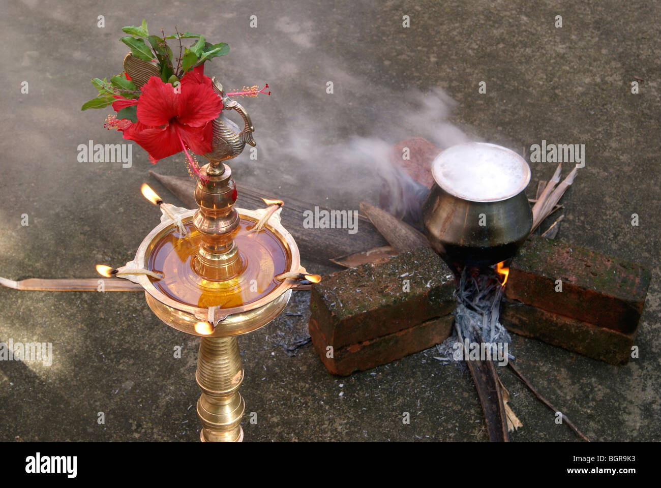 Tamil Pongal main dish payasam cooking in front of rising sun at early morning. well decorated lamp lighten up nearby. - Stock Image