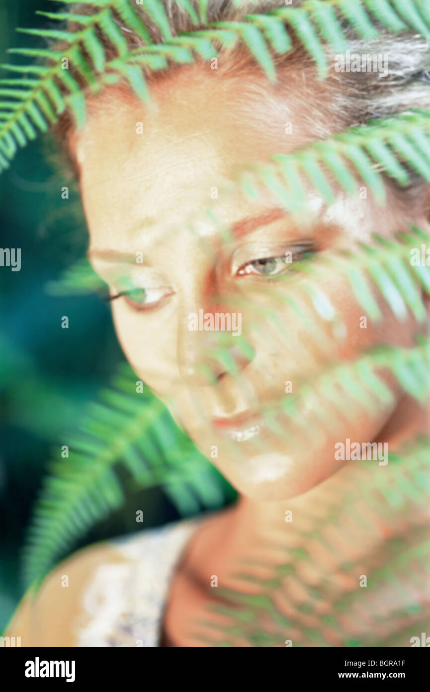 A face behind ferns, Bali. - Stock Image