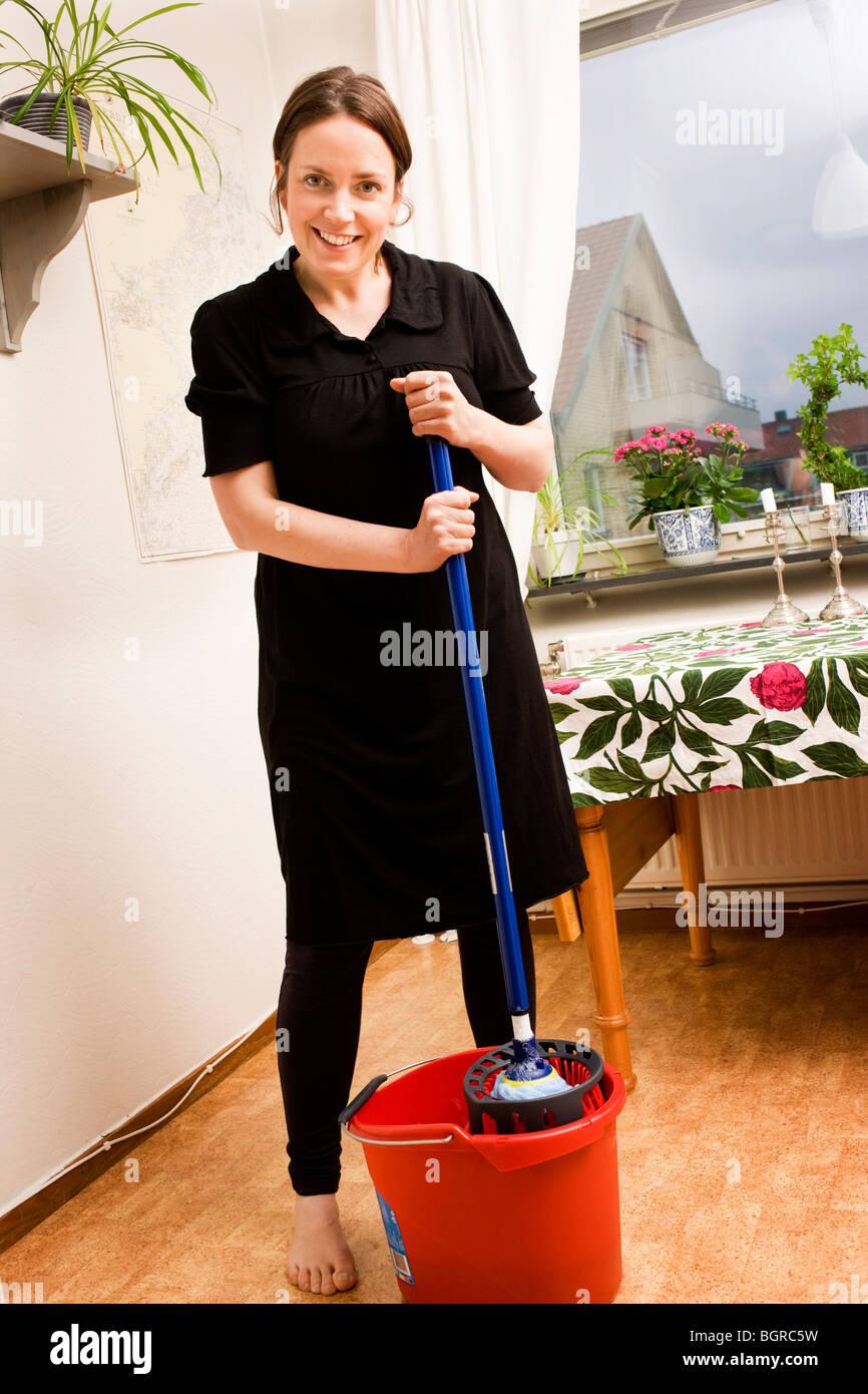 Woman scrubbing the floor, Sweden. - Stock Image