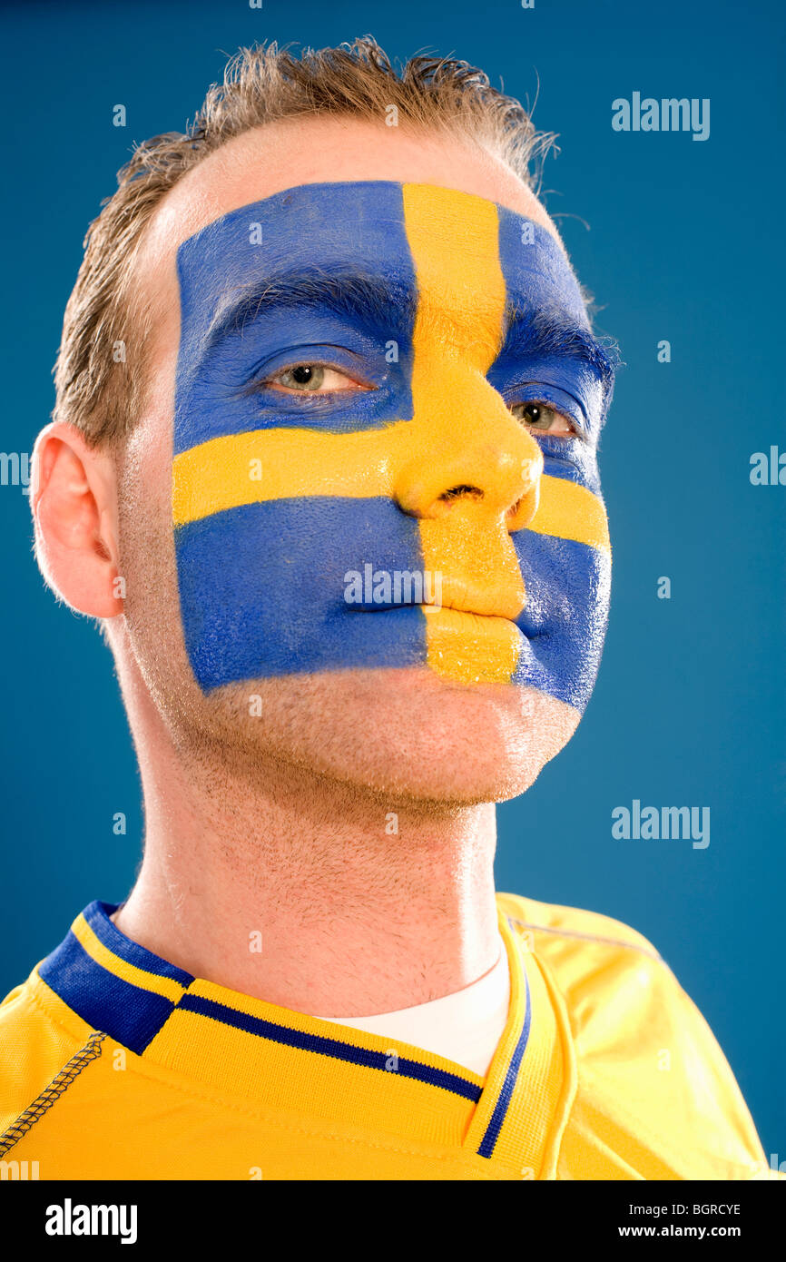 A man with the Swedish flag painted in his face. - Stock Image