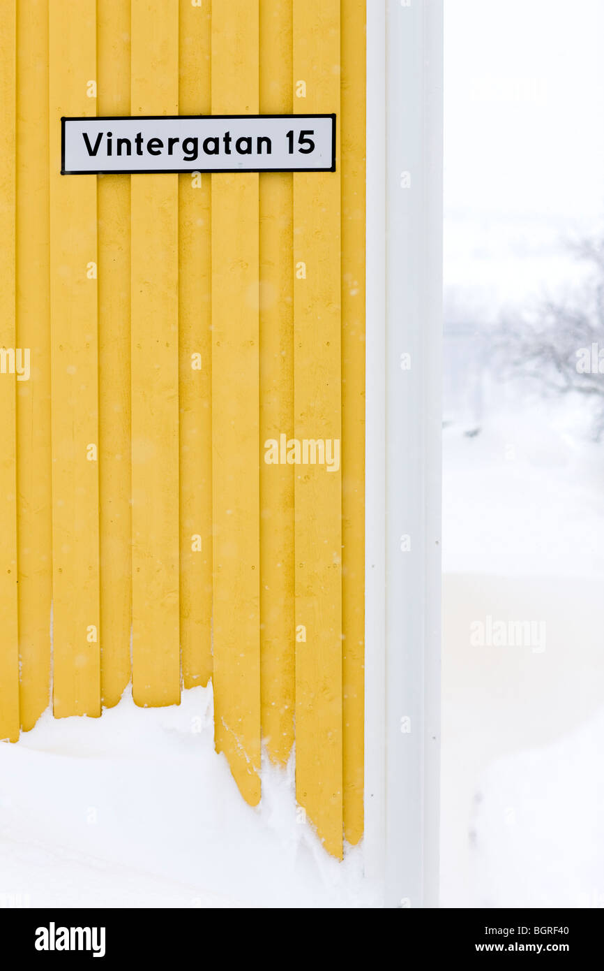 A street sign on a yellow wall, Sweden. - Stock Image