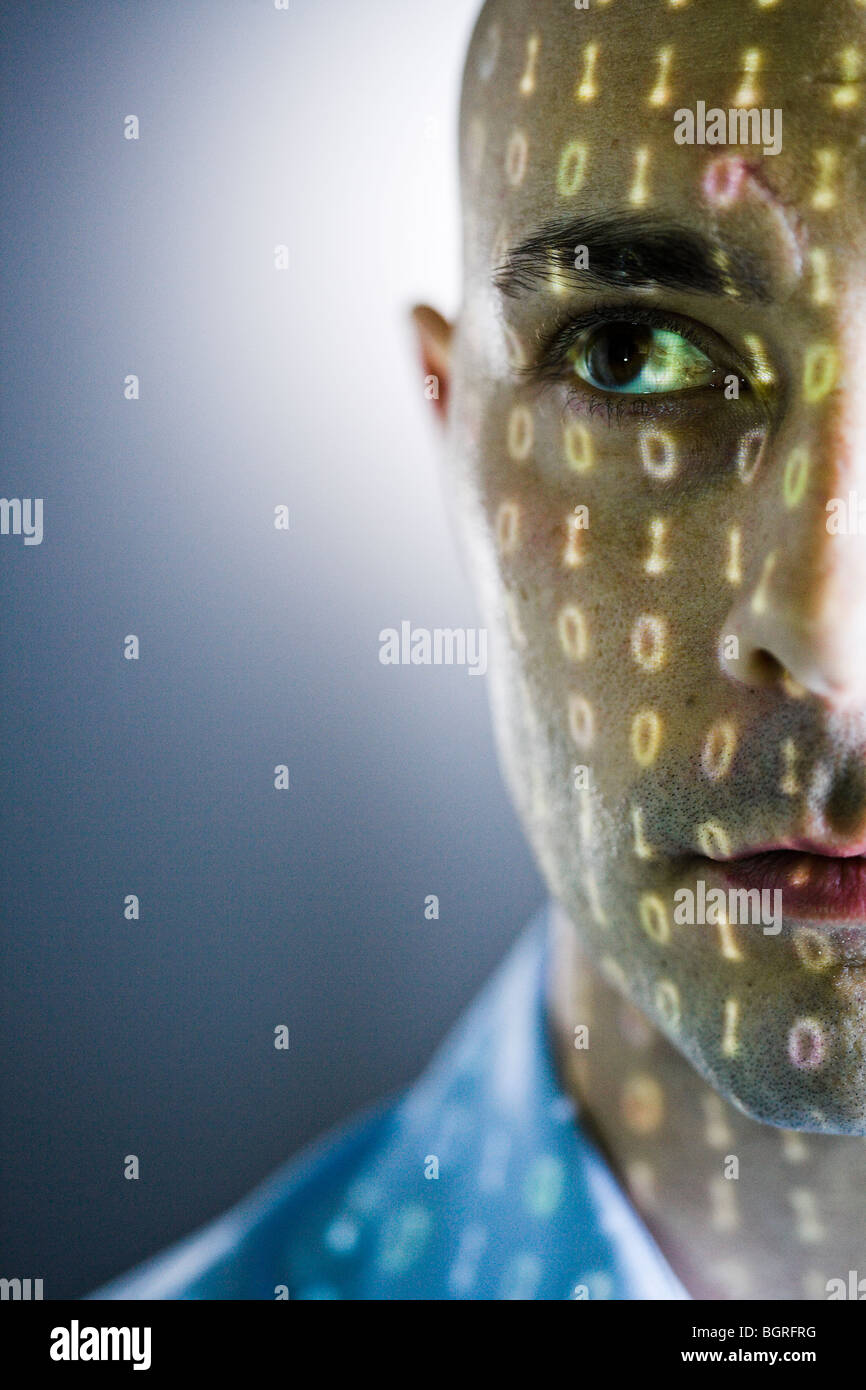Close-up of a man with digital numbers reflected on his face. - Stock Image