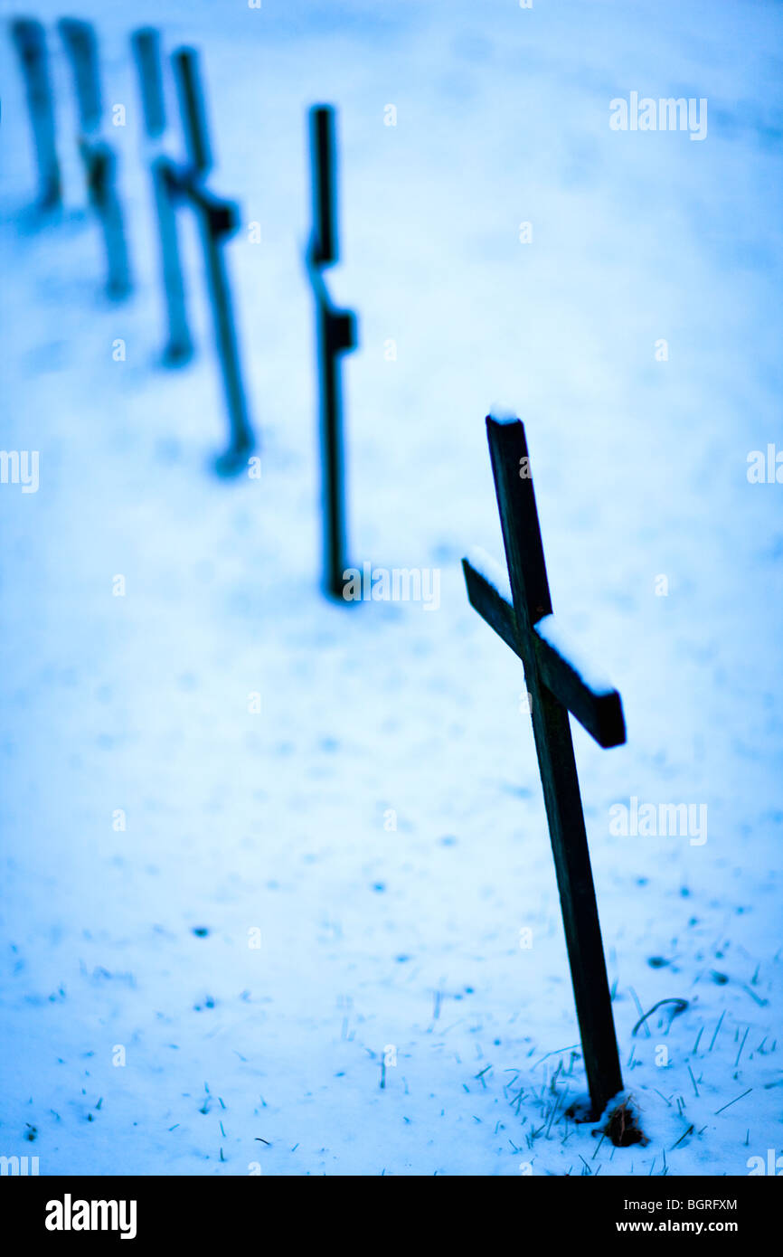 Cross on graves against the snow, Sweden. - Stock Image