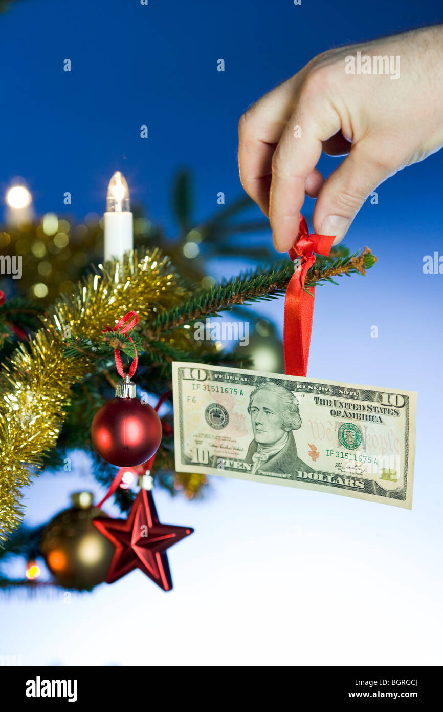 Christmas Tree Bill.A Dollar Bill Hanging In A Christmas Tree Stock Photo