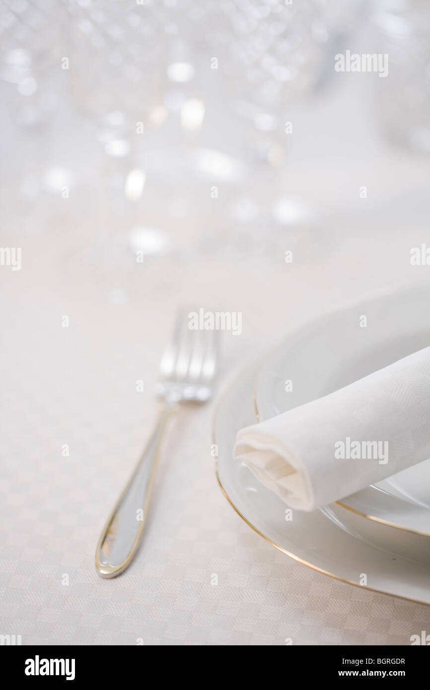 Table laid with white porcelain on a white table cloth. - Stock Image