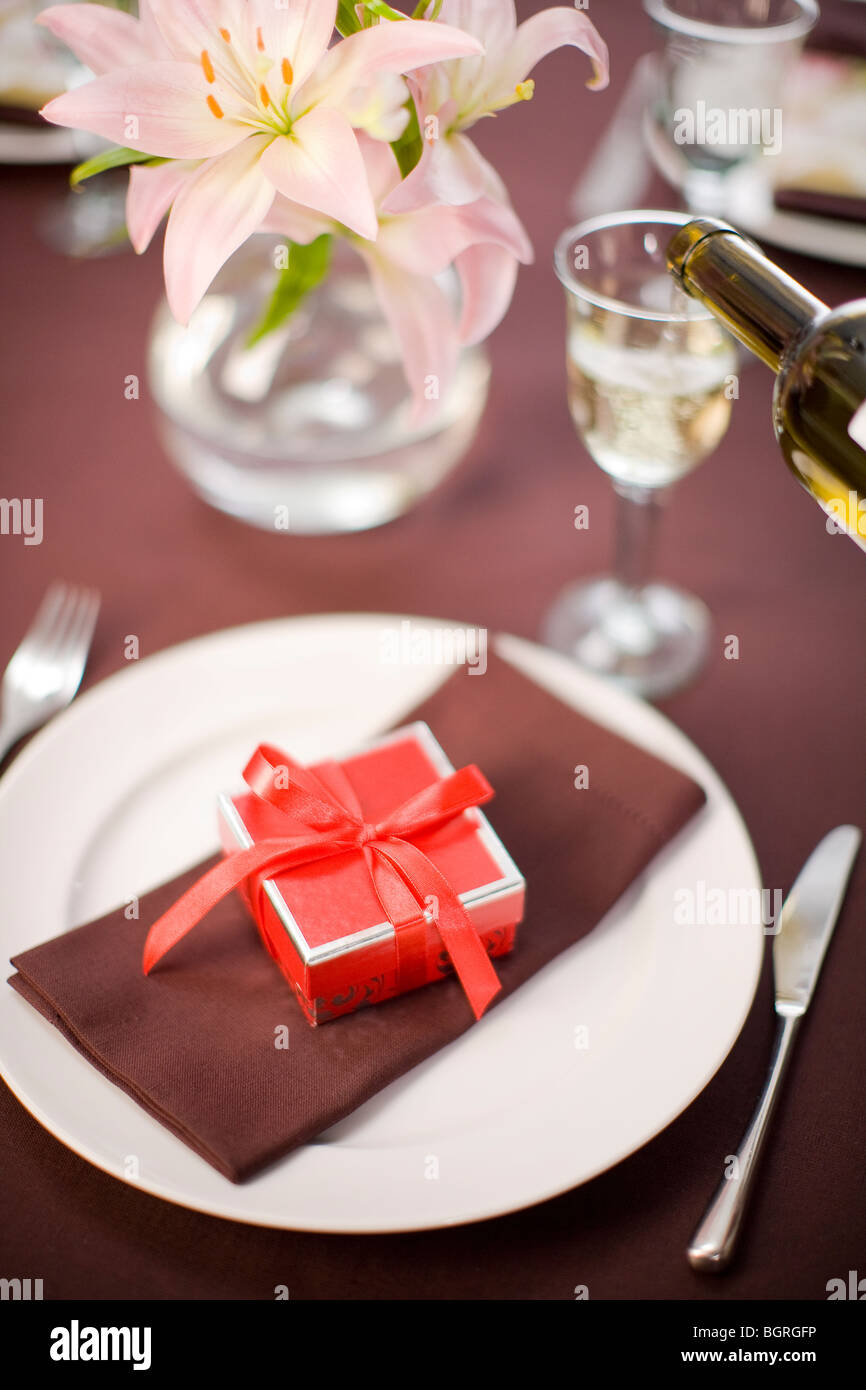 Table laid with a little red box on a plate. - Stock Image