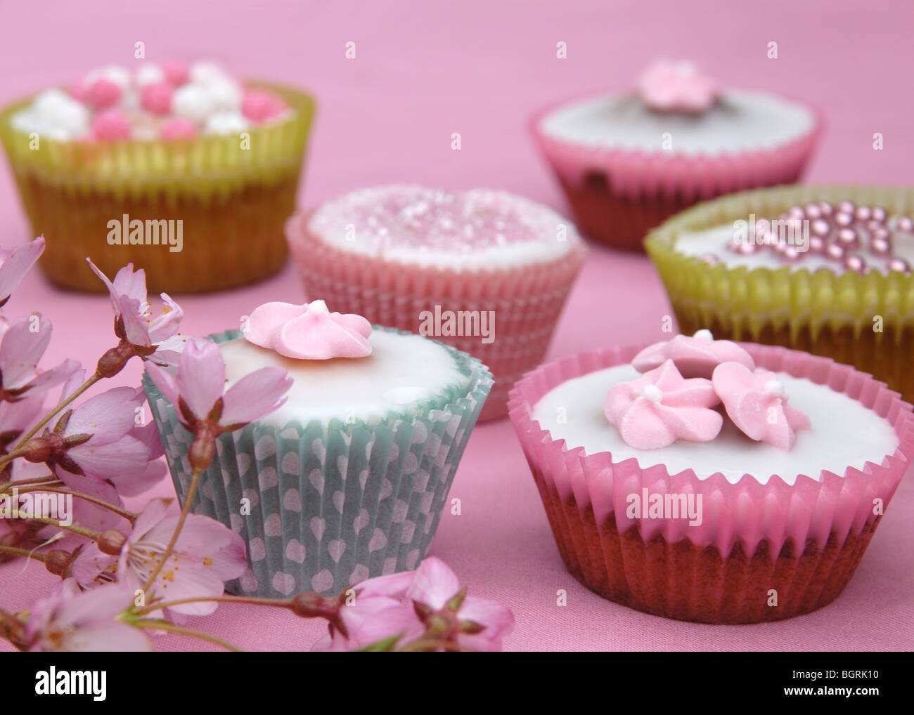 Close Up Of Six Pretty Decorated Cupcakes On A Pink