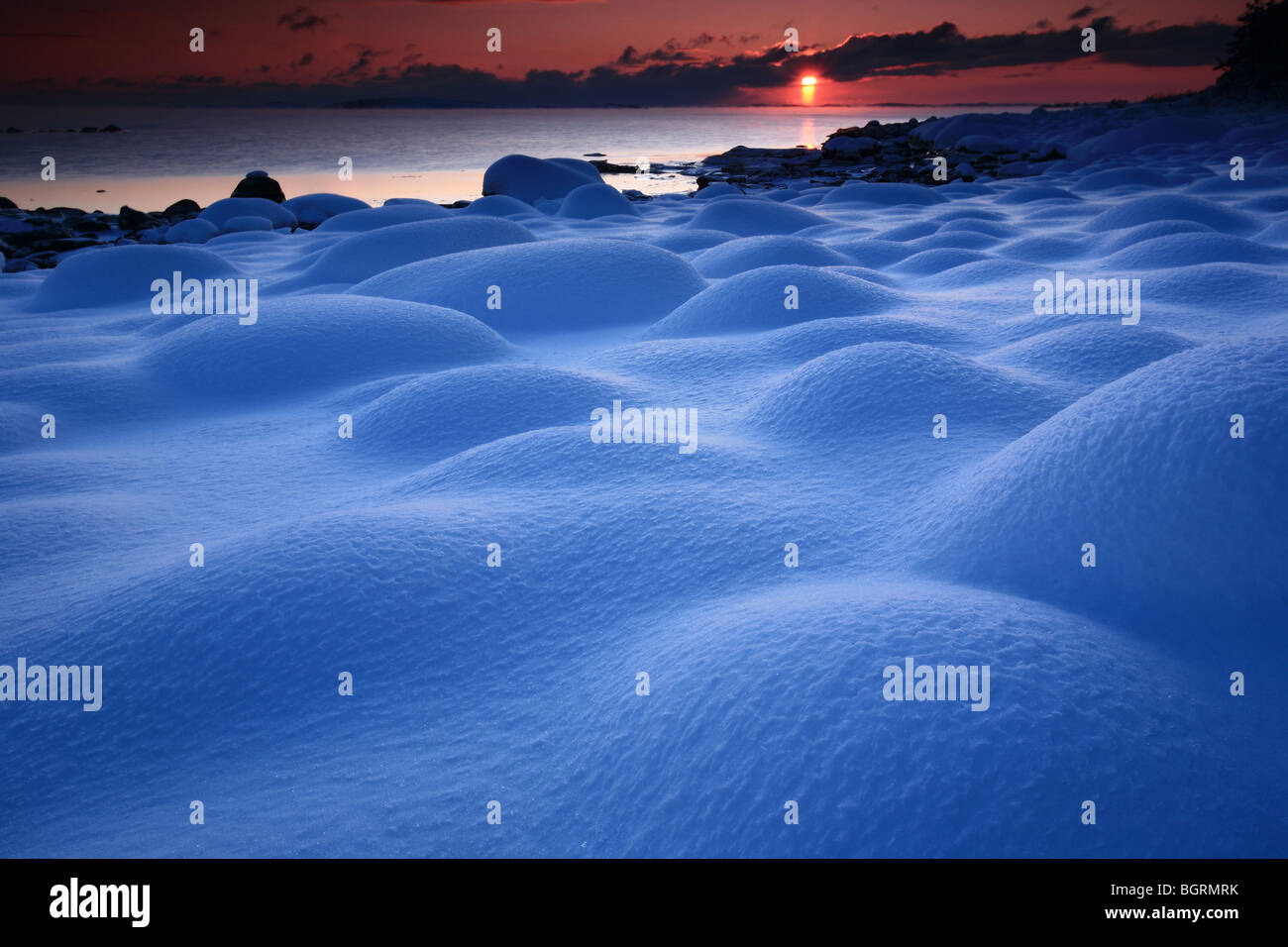 Snow covered rocks and sundown at Larkollen in Rygge kommune, Østfold fylke, Norway. - Stock Image