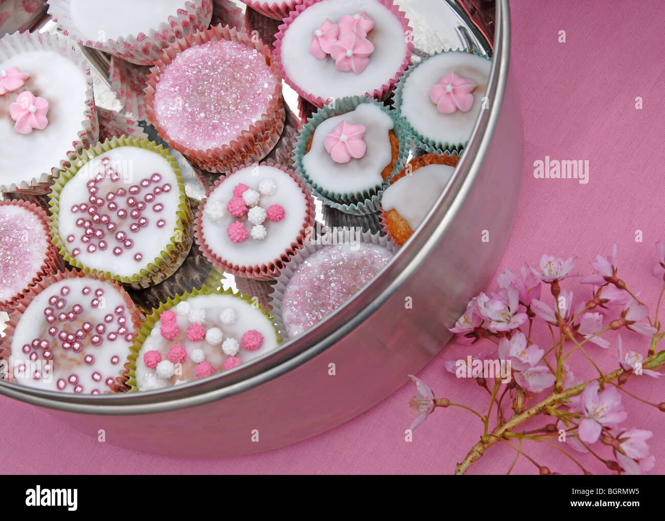 Silver cake tin with decorated fairy cakes on pink background with cherry blossom - Stock Image