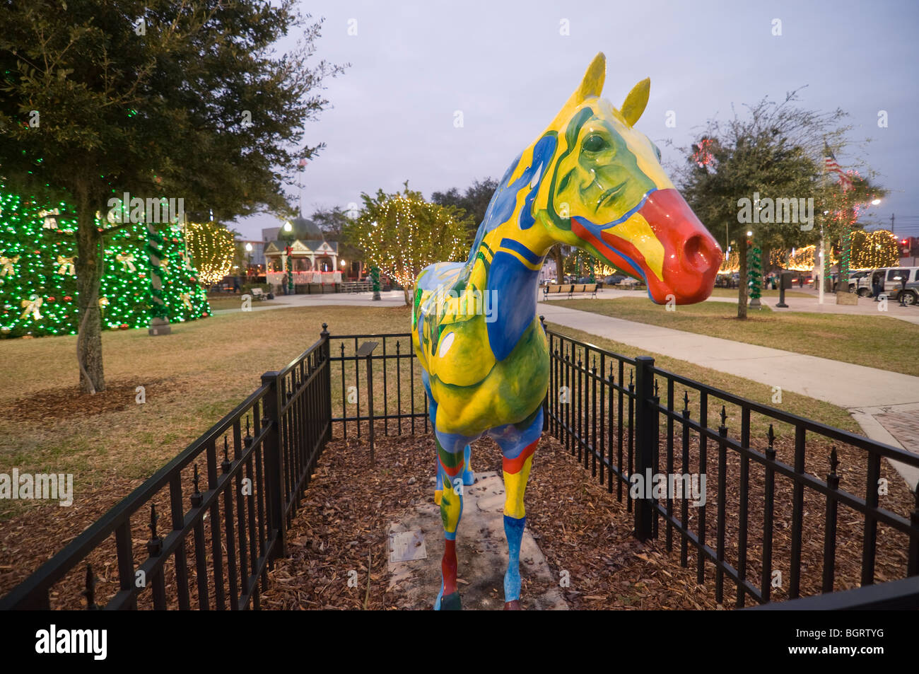Painted horse sculpture on display downtown square Ocala Florida among Christmas lights decorations - Stock Image