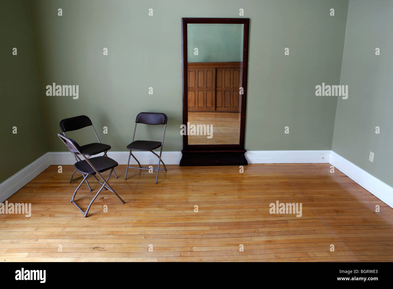 Empty room, three folding chairs, mirror, wood floors - Stock Image