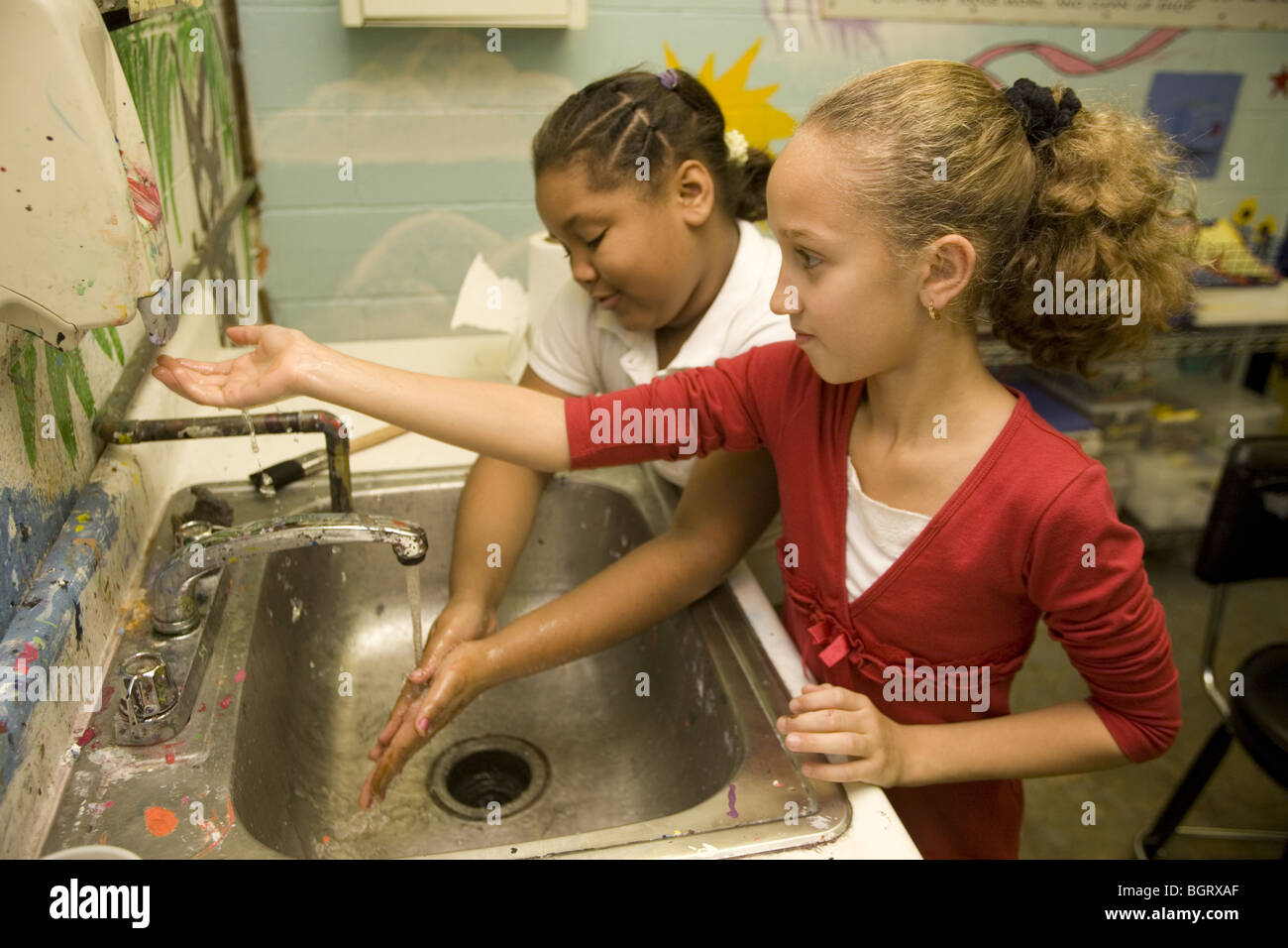 Girls wash up after an art class at an after school program at a community center in New York City. - Stock Image