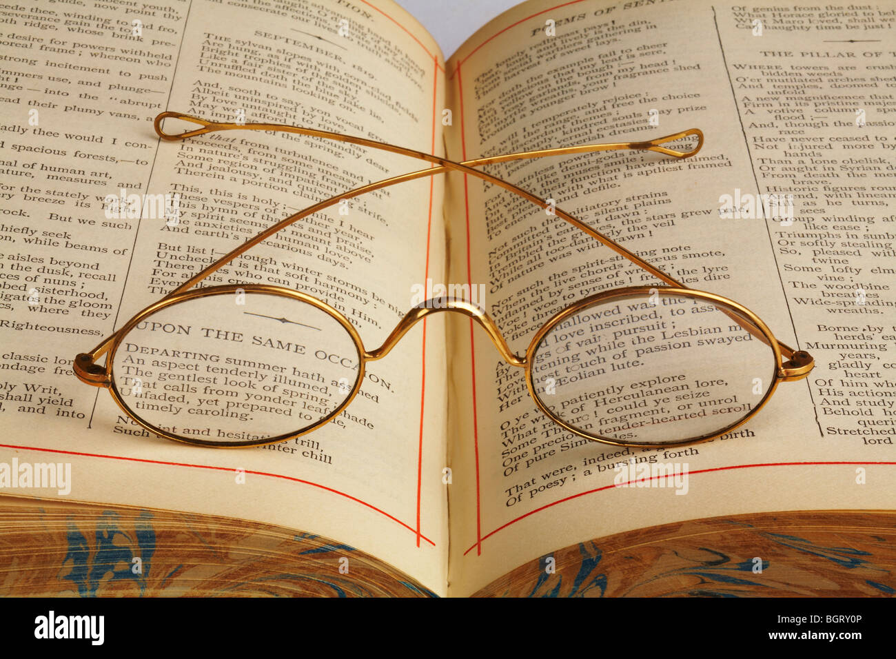antique gold rimmed spectacles laying across gutter of  open antique book of poems - Stock Image
