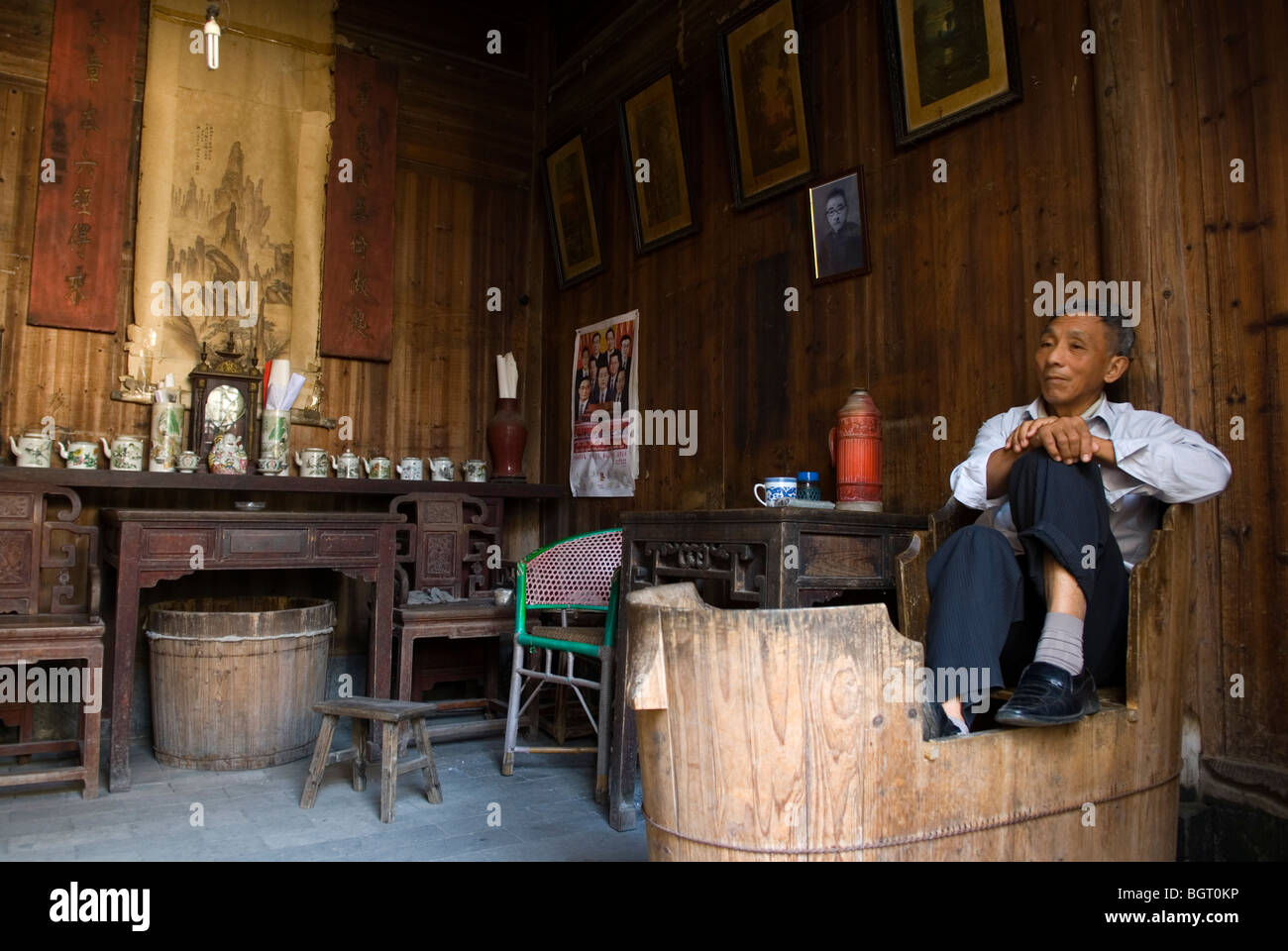 Interior of old merchant's house. Nanping, Anhui province. China. Male person sitting in an old wooden bathtub - Stock Image
